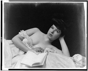 748px-Young_woman,_wearing_negligee,_lying_in_bed,_holding_book