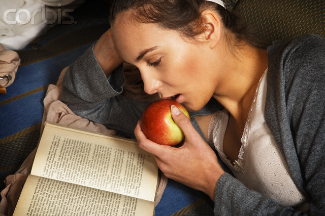 Woman Reading and Eating an Apple --- Image by © CKDJ/Corbis