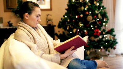 stock-footage-woman-reading-book-on-sofa-christmas-tree-in-background