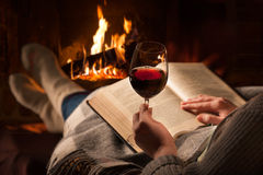 woman-reads-book-near-fireplace-resting-glass-red-wine-68573271