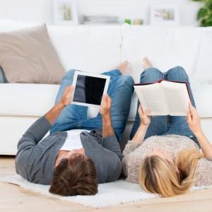 paar liest mit buch und tablet