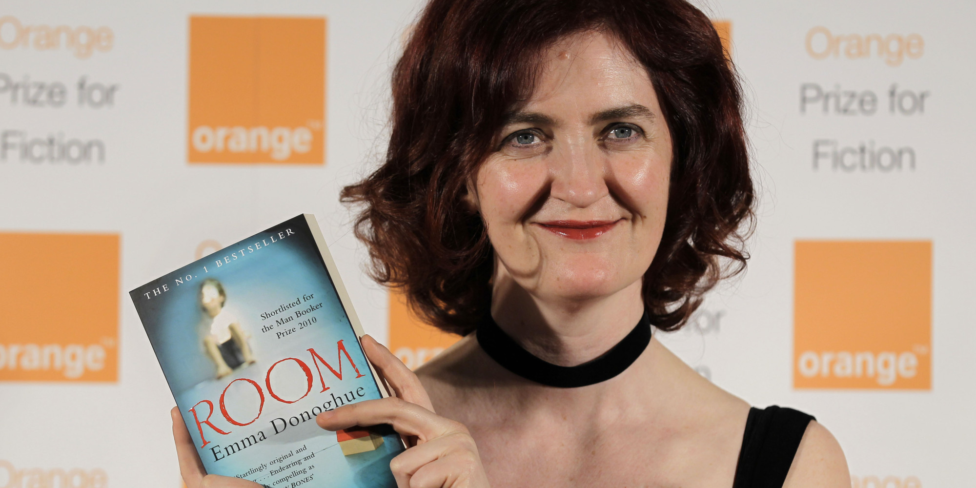 Shortlisted Irish author Emma Donoghue poses with her book 'Room' before the announcement of the 2011 Orange Prize for Fiction, during the awards ceremony at the Royal Festival Hall in London, Wednesday, June 8, 2011. (AP Photo/Sang Tan)