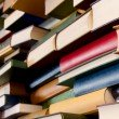 A lot of books stacked and forming a wall. Perspective.See also