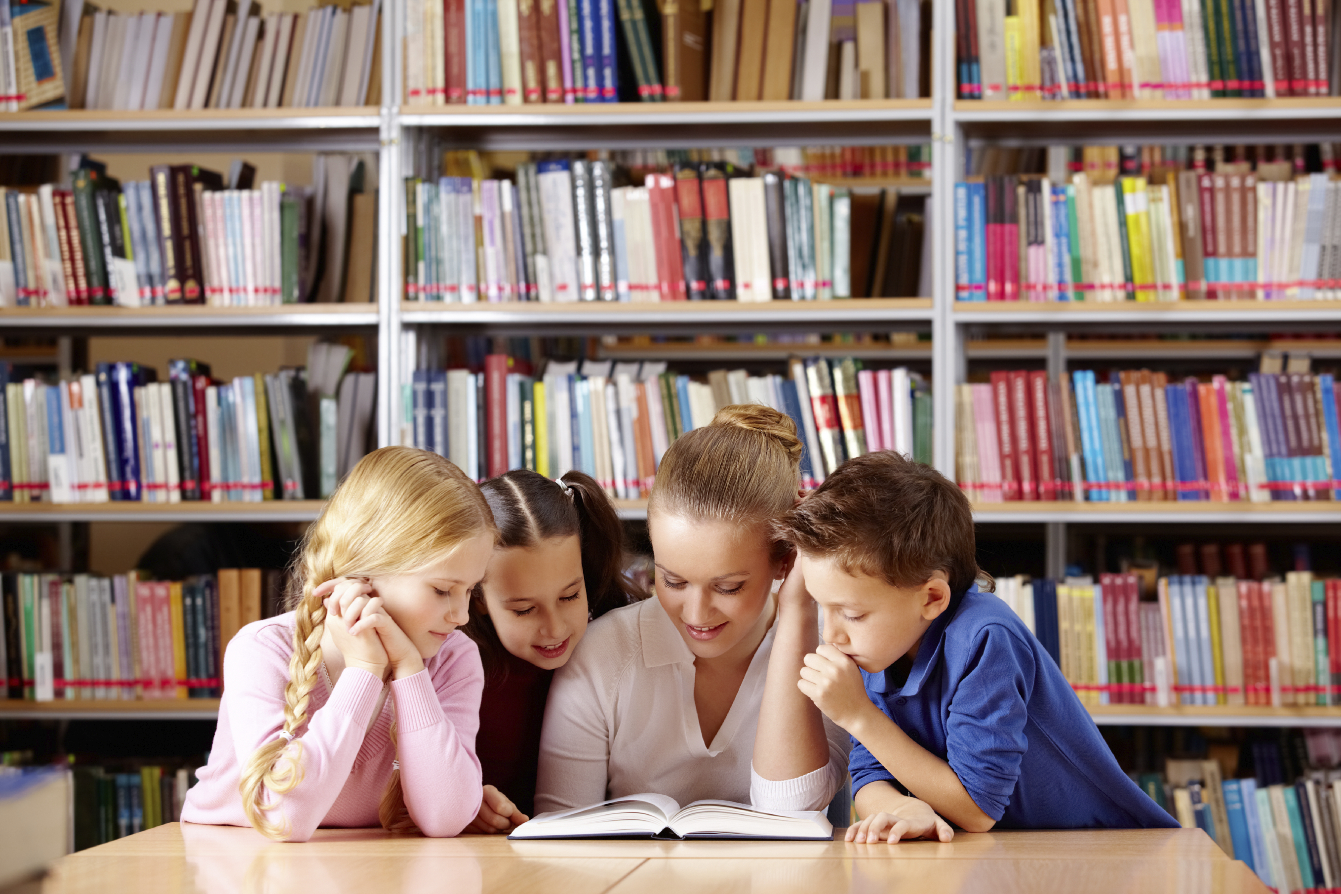 Portrait of pupils and teacher looking at page of interesting book in library