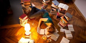 Young woman lying and sleeping on floor, surrounded by books --- Image by © Matthias Tunger/Corbis