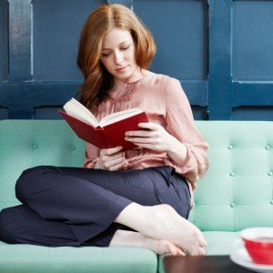 woman-reading-a-book-on-sofa--117845380-5977a22c519de200119d6f32