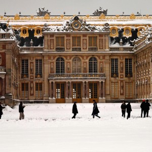 People walk past the snow-covered Palace of Versailles on February 7, 2018 in Versailles, outside of Paris.  Exceptionally heavy snowfall brought public transport in Paris and surrounding regions to a near halt on February 7, spelling misery for commuters after hundreds were forced to abandon their cars to sleep in emergency shelters overnight. / AFP PHOTO / CHRISTOPHE SIMONCHRISTOPHE SIMON/AFP/Getty Images