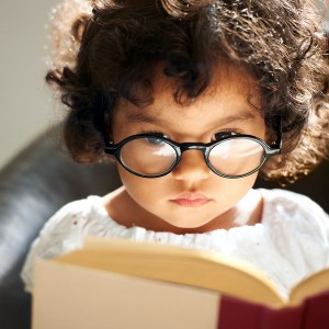 A cute little girl wearing glasses and reading a book