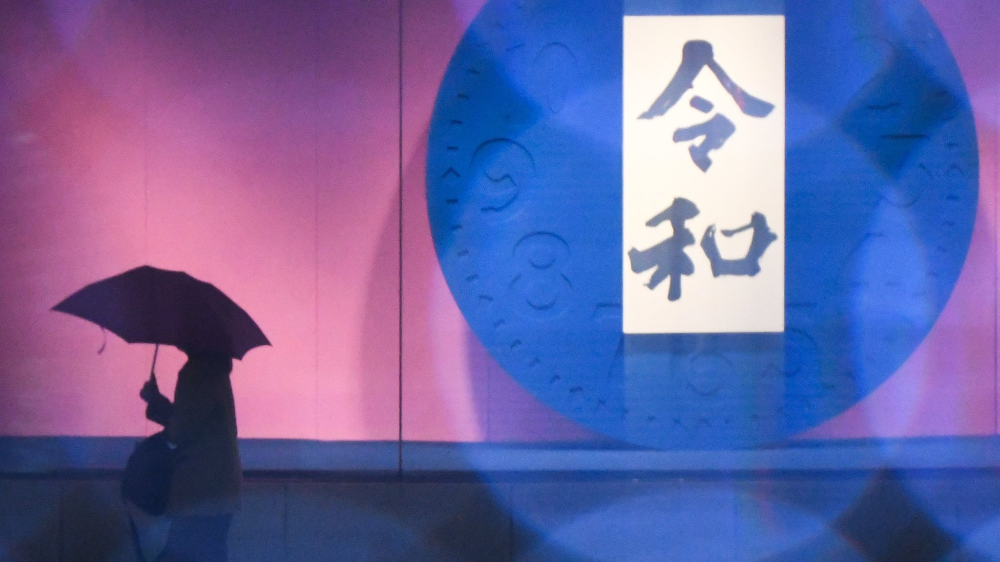 """01 April 2019, Japan, Tokyo: A woman walks past by the name of the Japanese new era """"Reiwa"""" which the country's new emperor Naruhito will reign. The word consists of two Japanese Kanji characters, """"Rei""""meaning order, command or good, while """"Wa"""" means harmony. Photo: Ramiro Agustin Vargas Tabares/ZUMA Wire/dpa"""