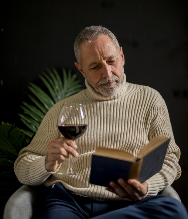 elderly-male-with-wine-reading-book_23-2148036726